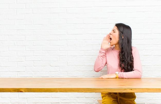 Młoda ładna kobieta z ameryki łacińskiej krzyczy głośno i ze złością do copyspace na boku, z ręką przy ustach siedzącą przed stołem