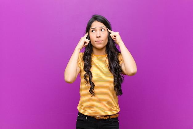 Młoda, ładna kobieta z ameryki łacińskiej, skoncentrowana i intensywnie zastanawiająca się nad pomysłem, wyobrażająca sobie rozwiązanie problemu lub problemu z fioletową ścianą