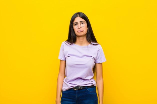 Młoda ładna kobieta z ameryki łacińskiej, smutna i płaczliwa z nieszczęśliwym spojrzeniem, płacząca z negatywnym i sfrustrowanym podejściem do ściany