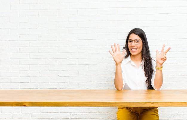 Młoda ładna kobieta z ameryki łacińskiej, uśmiechnięta i wyglądająca przyjaźnie, pokazująca numer osiem lub ósmy ręką do przodu, odliczająca czas siedząca przed stołem