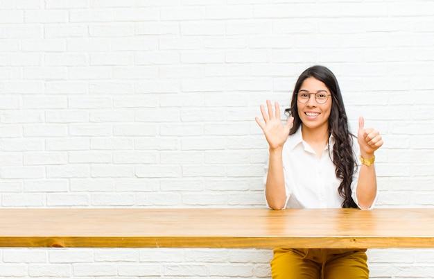 Młoda ładna kobieta z ameryki łacińskiej, uśmiechnięta i wyglądająca przyjaźnie, pokazująca numer szósty lub szósty ręką do przodu, odliczająca czas siedząca przed stołem