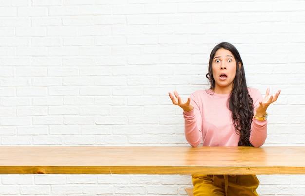 Młoda ładna kobieta z ameryki łacińskiej, wyglądająca na zdesperowaną i sfrustrowaną, zestresowaną, nieszczęśliwą i zirytowaną, krzyczącą i krzyczącą siedzącą przed stołem