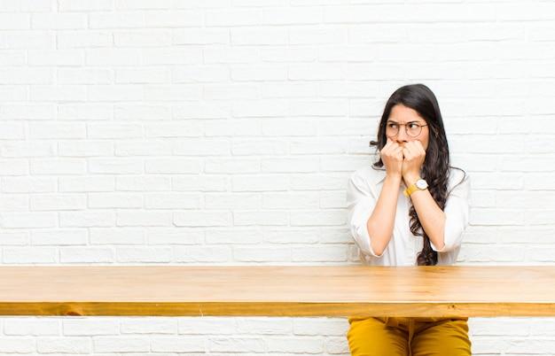 Młoda ładna kobieta z ameryki łacińskiej, wyglądająca na zmartwioną, niespokojną, zestresowaną i przestraszoną, obgryzająca paznokcie i patrząca na boczną przestrzeń kopii siedzącą przed stołem