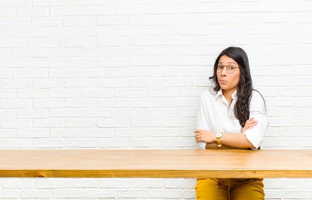 Młoda ładna kobieta z ameryki łacińskiej wzrusza ramionami, czuje się zagubiona i niepewna, wątpi ze skrzyżowanymi rękami i zdziwionym spojrzeniem siedząca przed stołem