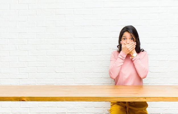 Młoda ładna kobieta z ameryki łacińskiej zakrywająca usta dłońmi z zszokowanym, zdziwionym wyrazem twarzy, utrzymująca tajemnicę lub mówiąc: ups siedzi przed stołem