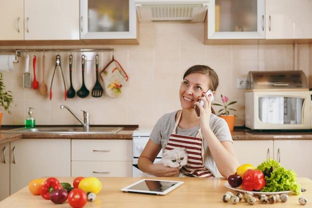Młoda ładna kobieta z białym kotem perskim rozmawia przez telefon komórkowy w kuchni z tabletem na stole. sałatka warzywna. koncepcja diety. zdrowy tryb życia. gotowanie w domu. przygotuj jedzenie.