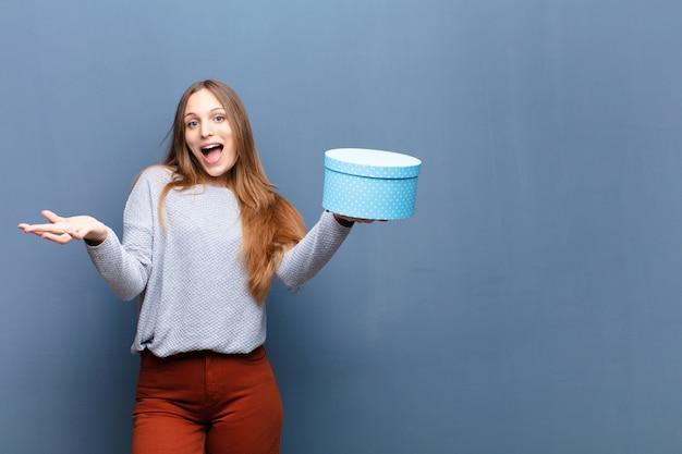 Młoda ładna kobieta z błękitnym pudełkiem nad błękit ścianą z odbitkową przestrzenią