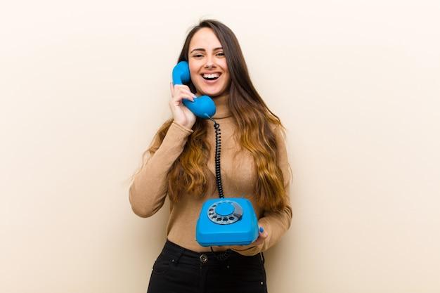 Młoda ładna kobieta z błękitnym rocznika telefonem