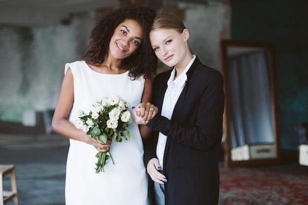 Młoda ładna kobieta z blond włosami w czarnym garniturze i piękna afroamerykanka z ciemnymi kręconymi włosami w białej sukni z bukietem kwiatów szczęśliwie na ceremonii ślubnej