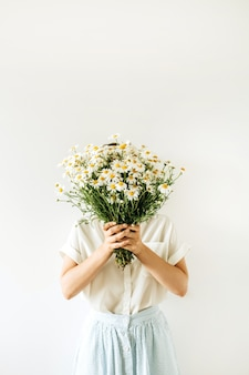 Młoda ładna kobieta z bukietem białych kwiatów rumianku