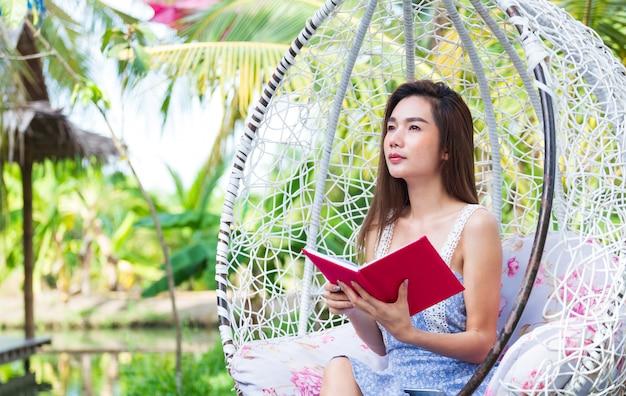 Młoda ładna kobieta z czerwonym dzienniczkiem w parku