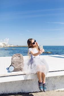 Młoda ładna kobieta z długimi włosami siedzi na molo