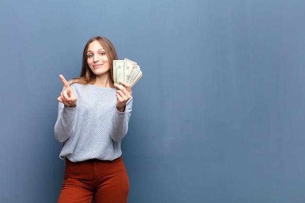 Młoda ładna kobieta z dolarowymi banknotami przeciw błękit ścianie z copyspace
