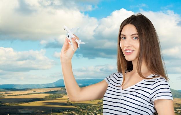 Młoda ładna kobieta z drewnianym zabawkarskim samolotem. koncepcja transportu lub podróży