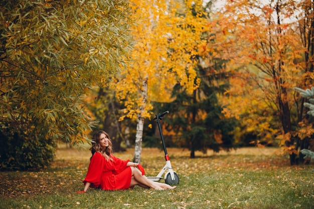 Młoda ładna kobieta z elektryczną hulajnogą w czerwonej sukience siedzi na trawie w jesiennym parku miejskim