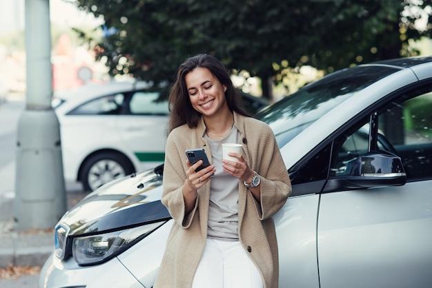 Młoda ładna kobieta z filiżanką kawy i pisaniem bloga na tablecie w jesiennym parku w pobliżu pojazdu