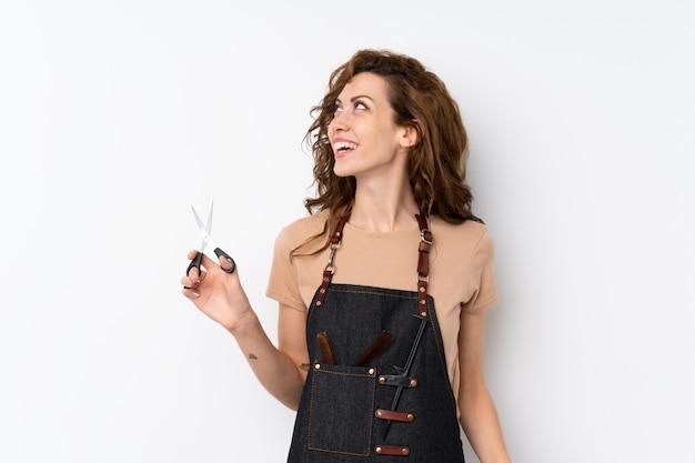 Młoda ładna kobieta z fryzjer lub fryzjer sukienka patrząc w górę