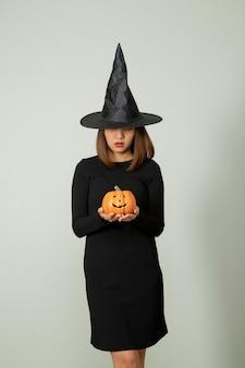 Młoda ładna kobieta z kapeluszem czarownicy, trzymając halloween dyni jack o lampion wystrój