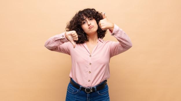 Młoda ładna kobieta z kręconymi włosami i różową koszulą