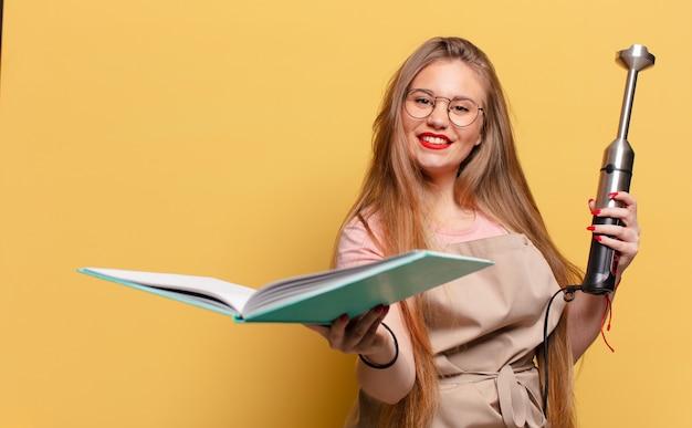 Młoda ładna kobieta z książką kucharską i mikserem