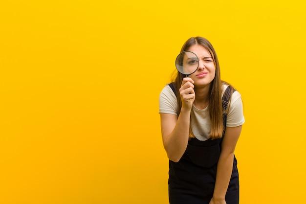 Młoda ładna kobieta z lupą pomarańczowy
