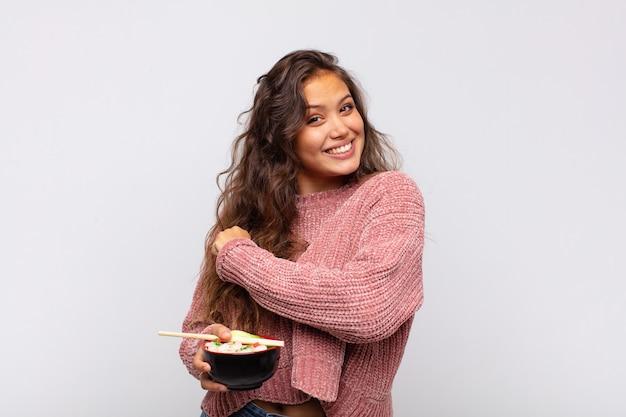 Młoda ładna kobieta z makaronem czuje się szczęśliwa, pozytywna i odnosząca sukcesy, zmotywowana, gdy staje przed wyzwaniem lub świętuje dobre wyniki
