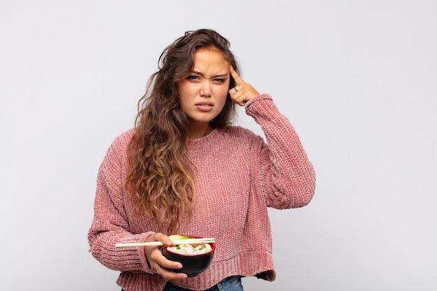 Młoda ładna kobieta z makaronem czuje się zdezorientowana i zakłopotana, pokazując, że jesteś szalony, szalony lub oszalały