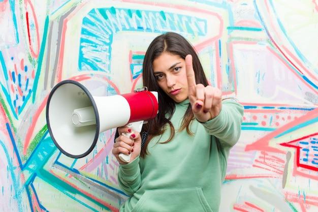 Młoda ładna kobieta z megafonem graffiti ściany