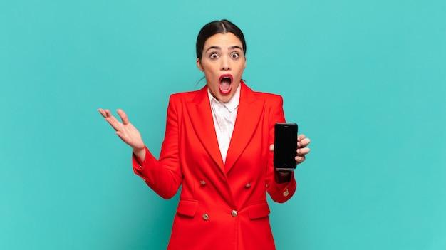 Młoda ładna kobieta z otwartymi ustami i zdumiona, zszokowana i zdumiona niewiarygodną niespodzianką. koncepcja inteligentnego telefonu