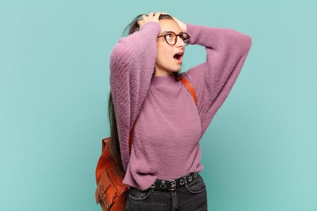 Młoda ładna kobieta z otwartymi ustami, wyglądająca na przerażoną i zszokowaną straszliwym błędem, podnosząca ręce do głowy. koncepcja studenta