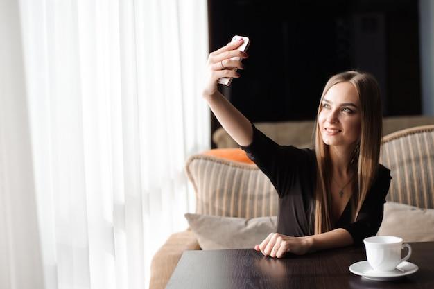 Młoda ładna kobieta z pięknym uśmiechem pozuje podczas gdy fotografujący się na kamery telefonu komórkowego.