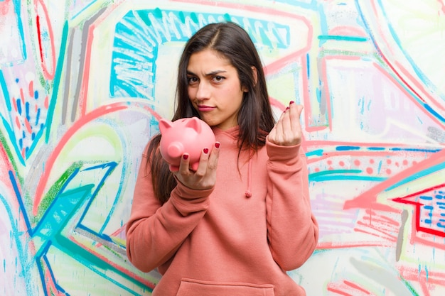 Młoda ładna kobieta z prosiątko bankiem przeciw graffiti ścianie
