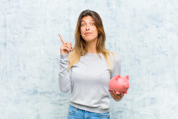 Młoda ładna kobieta z prosiątko bankiem przeciw grunge ścianie