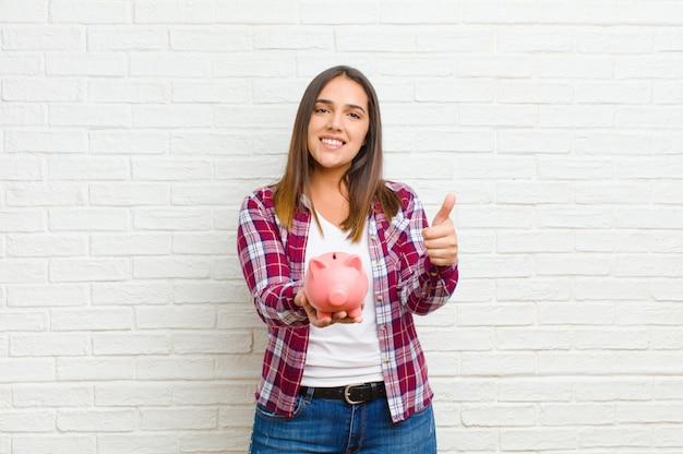 Młoda ładna kobieta z prosiątko bankiem przeciw ściana z cegieł teksturze