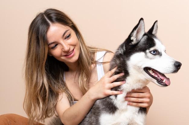 Młoda ładna kobieta z psem husky, siedząc na podłodze w pomieszczeniu