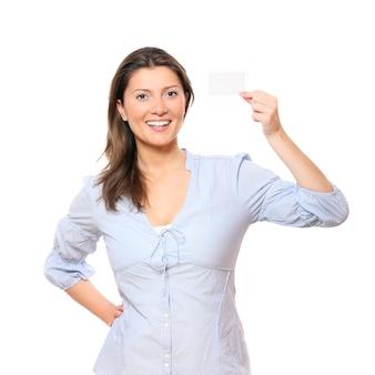 Młoda ładna kobieta z pustą wizytówką uśmiecha się na białym tle