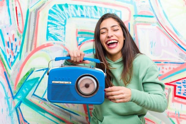 Młoda ładna kobieta z rocznika radiem przeciw graffiti ścianie