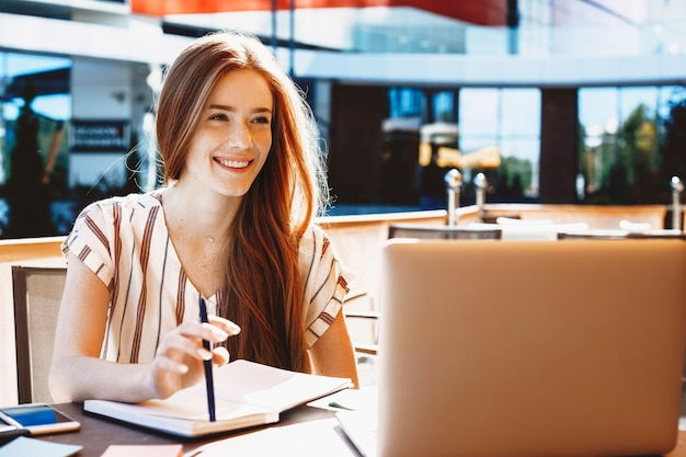 Młoda ładna kobieta z rudymi włosami robi treści wideo na swoim laptopie, siedząc w kawiarni na zewnątrz uśmiechając się.