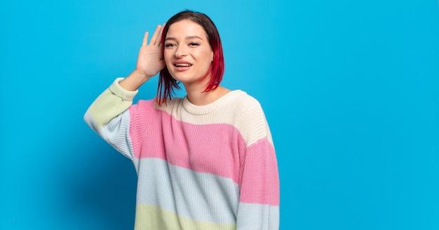 Młoda ładna kobieta z sweter w paski, pozowanie na niebieskiej ścianie