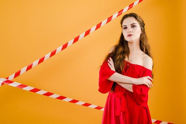 Młoda ładna kobieta z sygnałową taśmą odizolowywającą nad kolorem żółtym