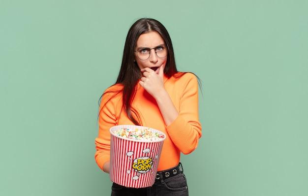 Młoda ładna kobieta z szeroko otwartymi ustami i oczami oraz ręką na brodzie, czując się nieprzyjemnie zszokowana, mówiąc co lub wow. koncepcja pop corns