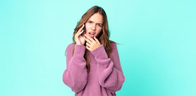 Młoda ładna kobieta z szeroko otwartymi ustami i oczami, z ręką na brodzie i używająca smartfona