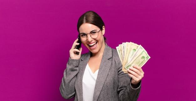Młoda ładna kobieta z telefonem i banknotami dolara. pomysł na biznes