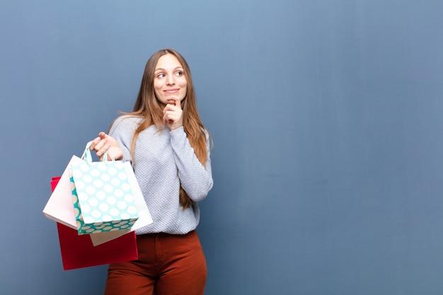 Młoda ładna kobieta z torba na zakupy przeciw błękit ścianie z odbitkową przestrzenią