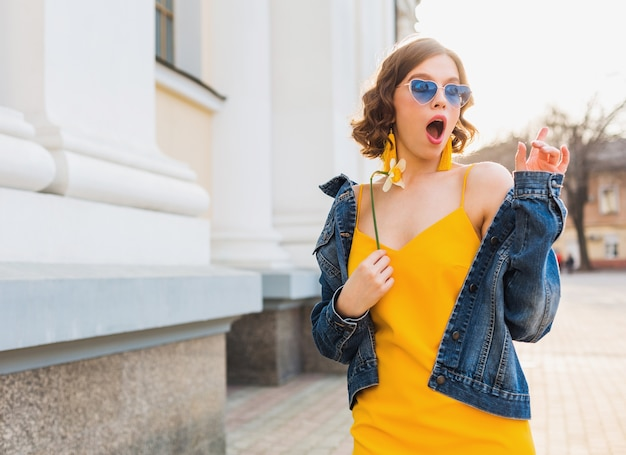 Młoda ładna kobieta z wyrazem zaskoczenia, emocjonalnym, zszokowanym uczuciem, w stylowej odzieży, dżinsowej kurtce, żółtym topie, trzymającym kwiatku, słoneczne lato, modne śmieszne okulary przeciwsłoneczne