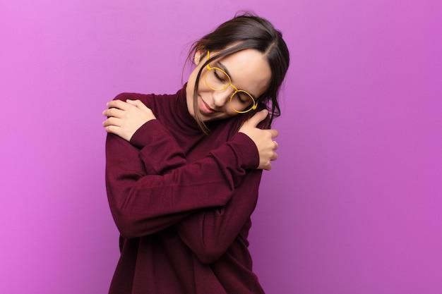 Młoda ładna kobieta zakochana, uśmiechnięta, przytulająca się i przytulająca, pozostająca singlem, będąca samolubna i egocentryczna wobec fioletowej ściany