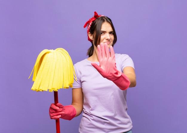 Młoda ładna kobieta zakrywa twarz dłonią i kładzie drugą rękę do przodu, aby zatrzymać aparat, odmawiając zdjęć lub zdjęć