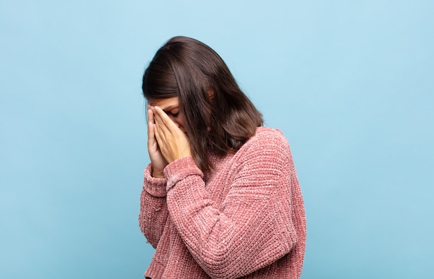 Młoda ładna kobieta zakrywająca oczy dłońmi ze smutnym, sfrustrowanym wyrazem rozpaczy, płaczu, widoku z boku