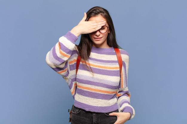 Młoda ładna kobieta zakrywająca oczy jedną ręką, czuje się przestraszona lub niespokojna, zastanawia się lub na ślepo czeka na niespodziankę