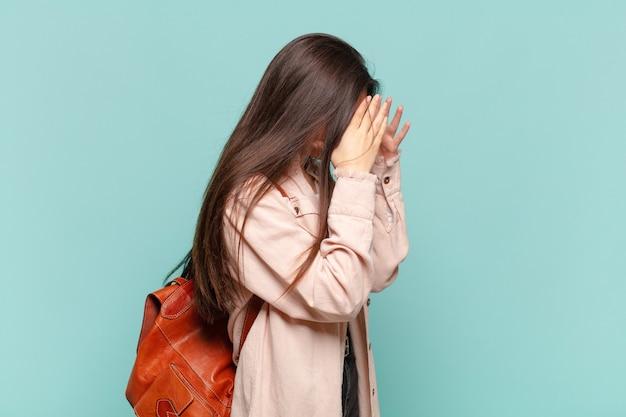Młoda ładna kobieta zakrywająca oczy rękami ze smutnym, sfrustrowanym wyrazem rozpaczy, płaczu, widok z boku. koncepcja studenta